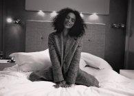 Девушка, сидящая на белой кровати — стоковое фото