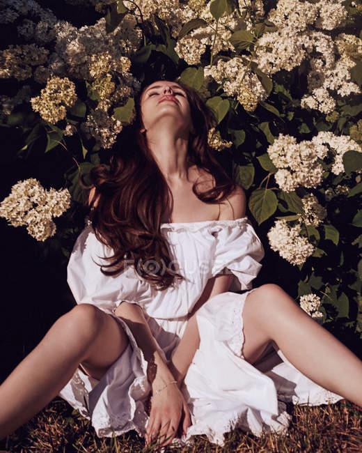 Женщина в платье сидит рядом с кустом цветов — стоковое фото
