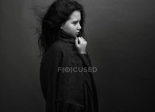 Ragazza in cappotto oversize guardando altrove — Foto stock