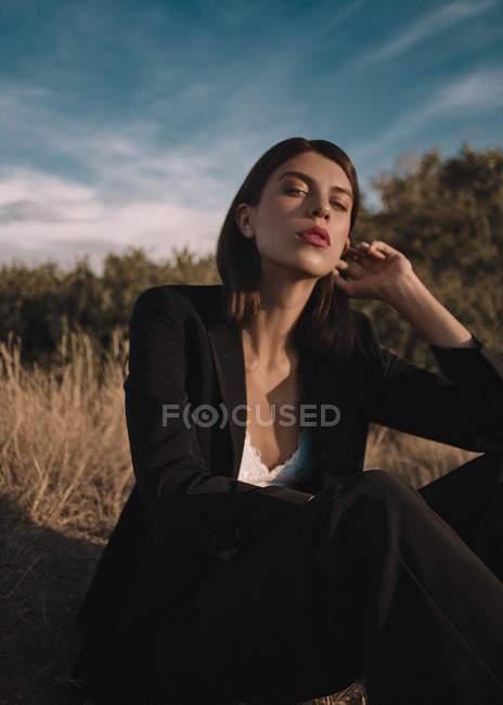 Femme assise dans la prairie et posant à la caméra — Photo de stock