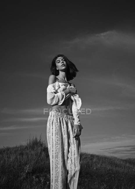 Женщина позирует на лугу с сельским пейзажем — стоковое фото
