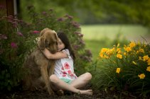 Chien étreignant belle fille dans le jardin — Photo de stock