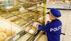 Boy in police costume choosing buns — Stock Photo