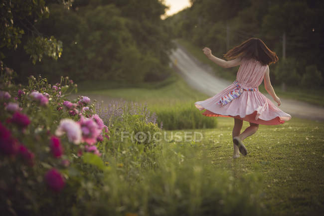 Girl in dress dancing on green lawn — Stock Photo