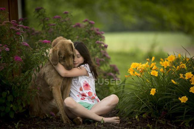 Beautiful girl hugging dog in garden — Stock Photo