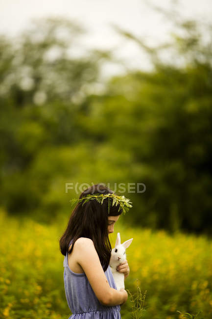 Girl in floral wreath holding rabbit — Stock Photo