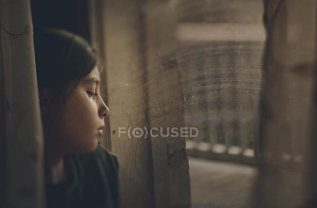 Ragazza premurosa guardando la finestra — Foto stock