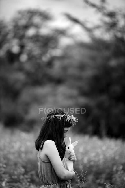 Девушка в цветочный венок, держа кролика — стоковое фото