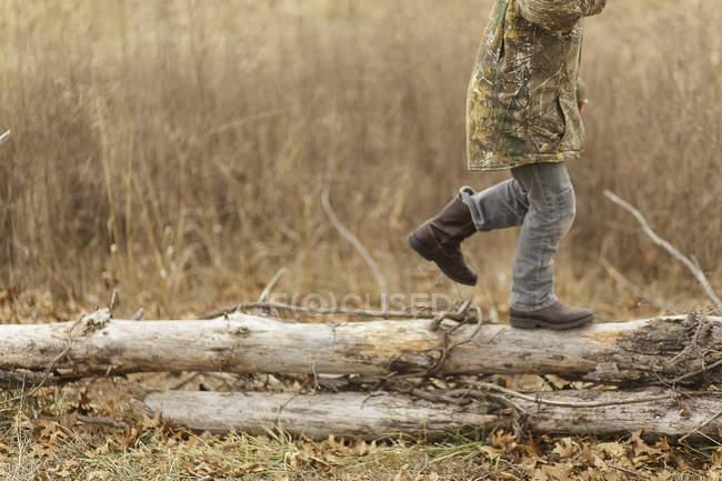 Мальчик бегает по сухим бревнам — стоковое фото