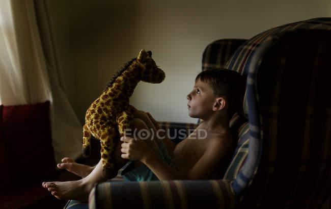Junge spielt mit Giraffenspielzeug — Stockfoto