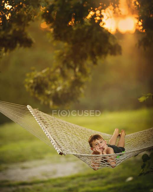 Adorable niñito acostado en hamaca - foto de stock