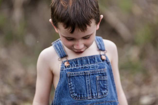 Симпатичный мальчик в джинсовом комбинезоне — стоковое фото