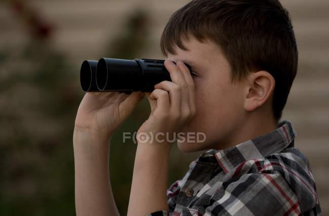 Милий хлопчик дивиться в бінокль — стокове фото