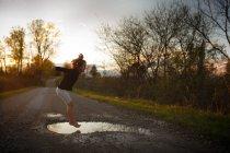 Mädchen in Pfütze springen — Stockfoto