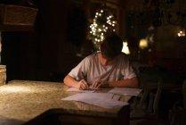 Хлопчик написання листа в темній кімнаті — стокове фото