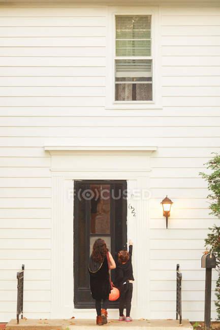 Girls at front door ringing doorbell — Stock Photo
