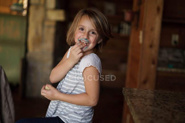 Mädchen mit blauem Zuckerguss im Gesicht — Stockfoto