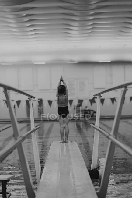 Girl standing at end of diving board — Stock Photo