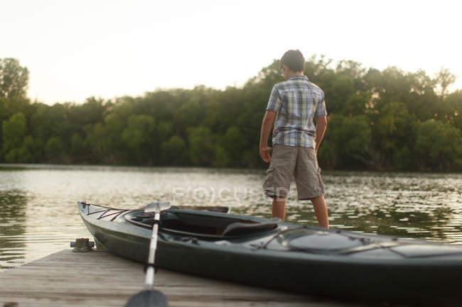 Boy with kayak and paddle at the lake — Stock Photo