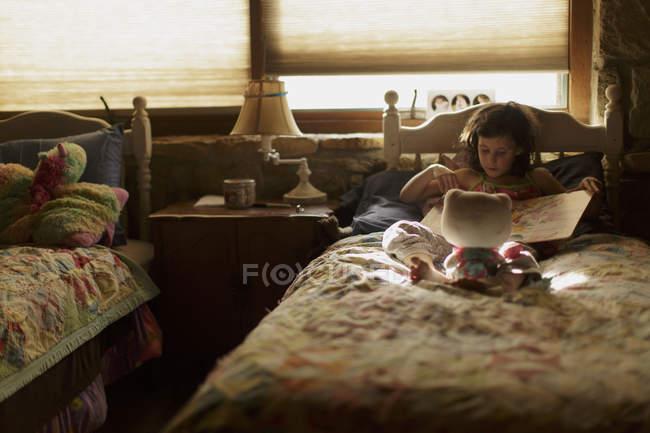 Kleines Mädchen liest Buch im Bett — Stockfoto