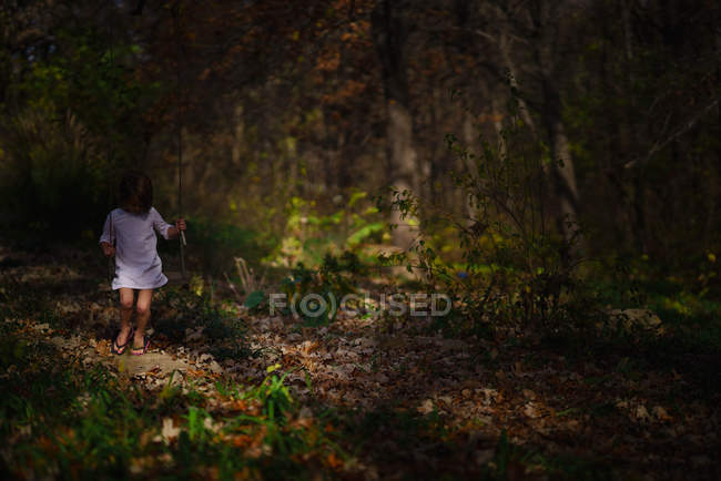 Girl on swing in autumn forest — Stock Photo