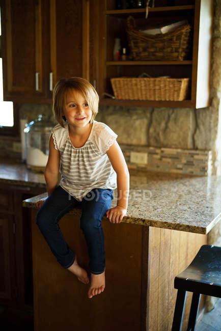 Девочка сидит на столе — стоковое фото