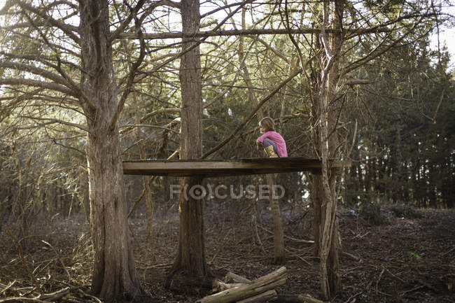 Fille assise sur la surface en bois entre les arbres — Photo de stock
