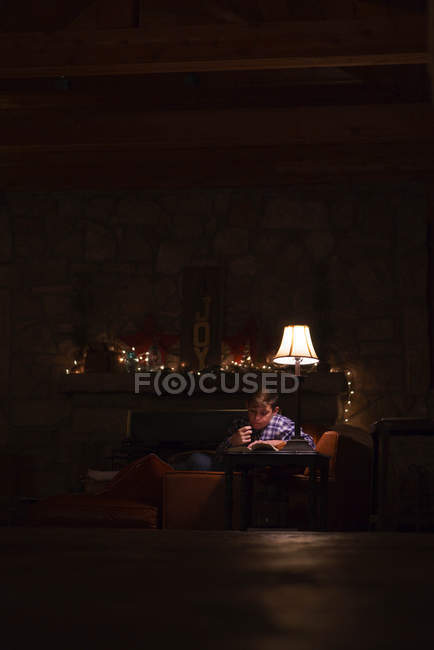 Boy reading book on coffee table — Stock Photo
