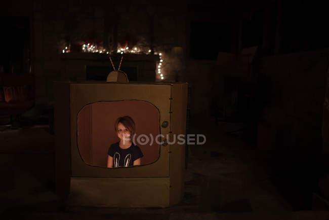 Menina dentro engraçado conjunto de tv de papelão — Fotografia de Stock