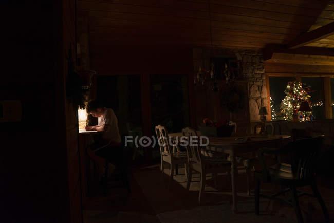 Junge schreibt Brief im dunklen Raum — Stockfoto