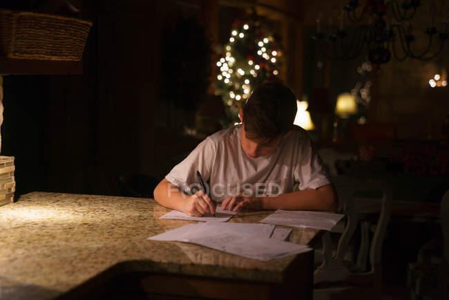 Menino escrevendo carta no quarto escuro — Fotografia de Stock