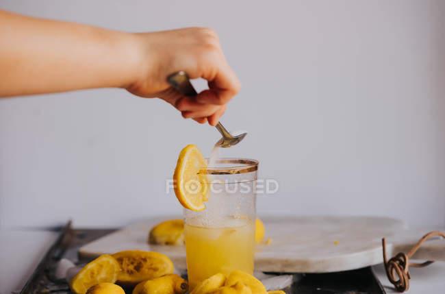 Ernte Hand Zugabe von Zucker zu Glas mit frischem Saft — Stockfoto