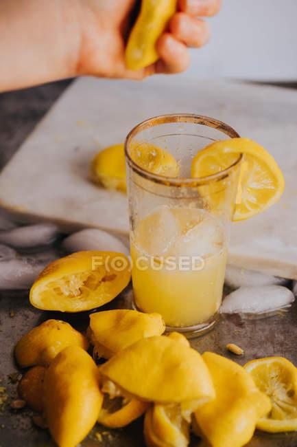 Zitronensaft von Hand in Glas pressen — Stockfoto