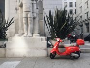 Red scooter on the sidewalk — Stock Photo