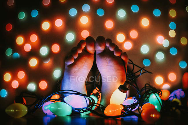 Human feet and colorful garland — Stock Photo