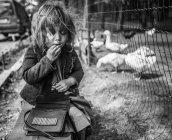 Девушка сидит и ест рядом с клеткой — стоковое фото