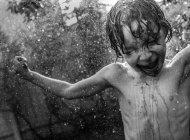 Boy under watering splashes — Stock Photo