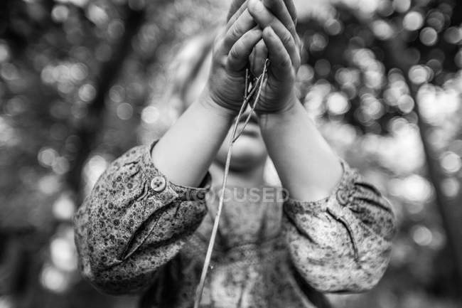 Girl holding twig in hands — Stock Photo