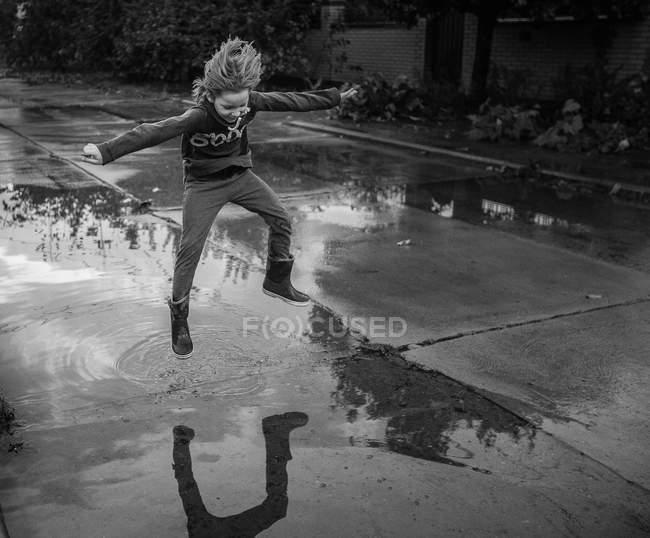 Ragazzo schizzi d'acqua su strada — Foto stock