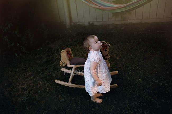 Petit bébé debout près du cheval jouet — Photo de stock
