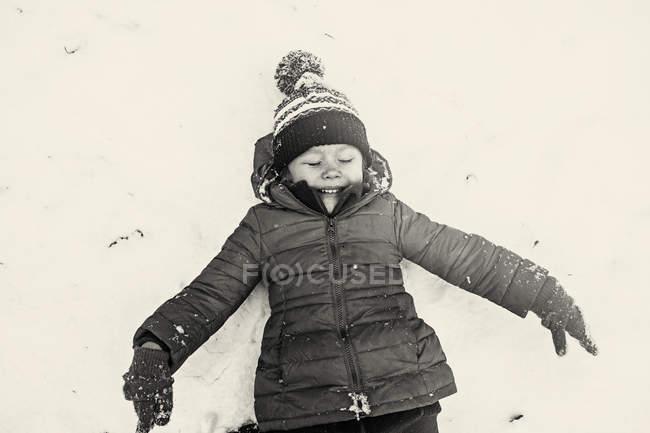 Smiling girl lying in snow — Stock Photo