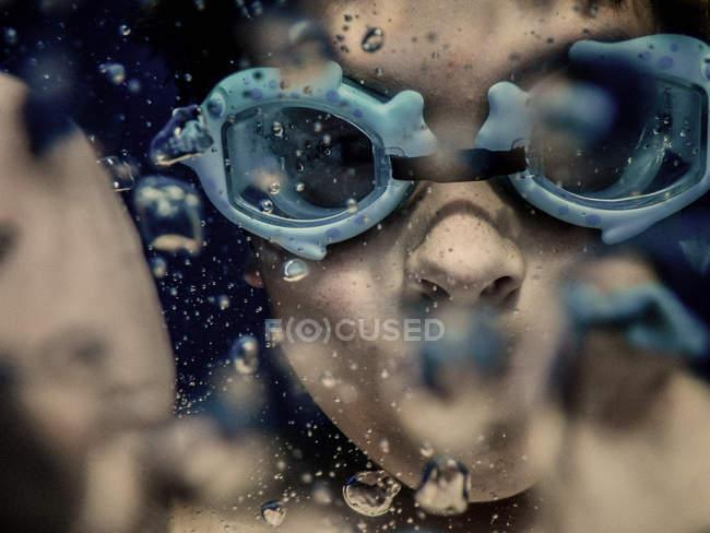 Garoto no googles a nadar debaixo de água — Fotografia de Stock