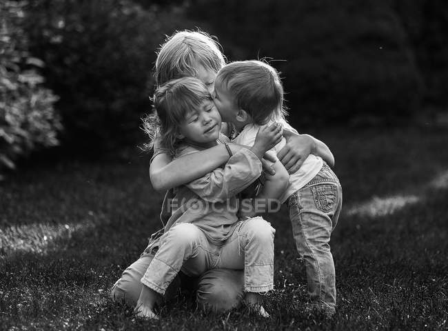 Kids hugging on meadow — Stock Photo