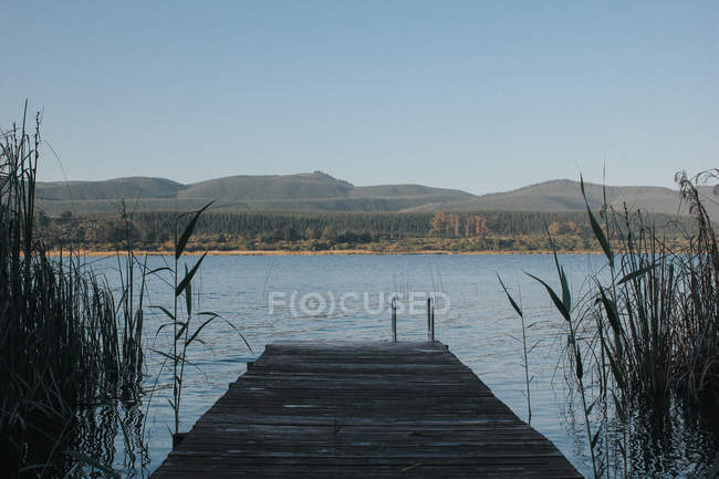 Empty wooden pier with mountain landscape — Stock Photo