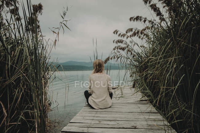 Girl sitting on wooden jetty — Stock Photo