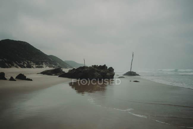 Costa rochosa, com praia de areia — Fotografia de Stock