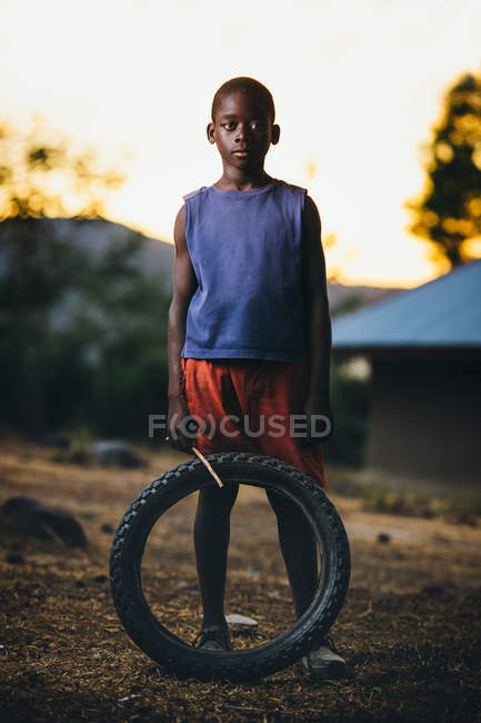 African boy with stick and wheel — Stock Photo