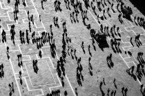 Silhuetas de pessoas em uma grande praça — Fotografia de Stock