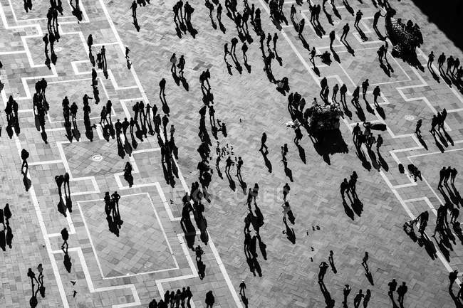 Silhouettes of people in a large plaza — Stock Photo