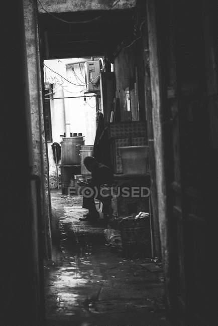 Человек, сидящий на узкой улице — стоковое фото
